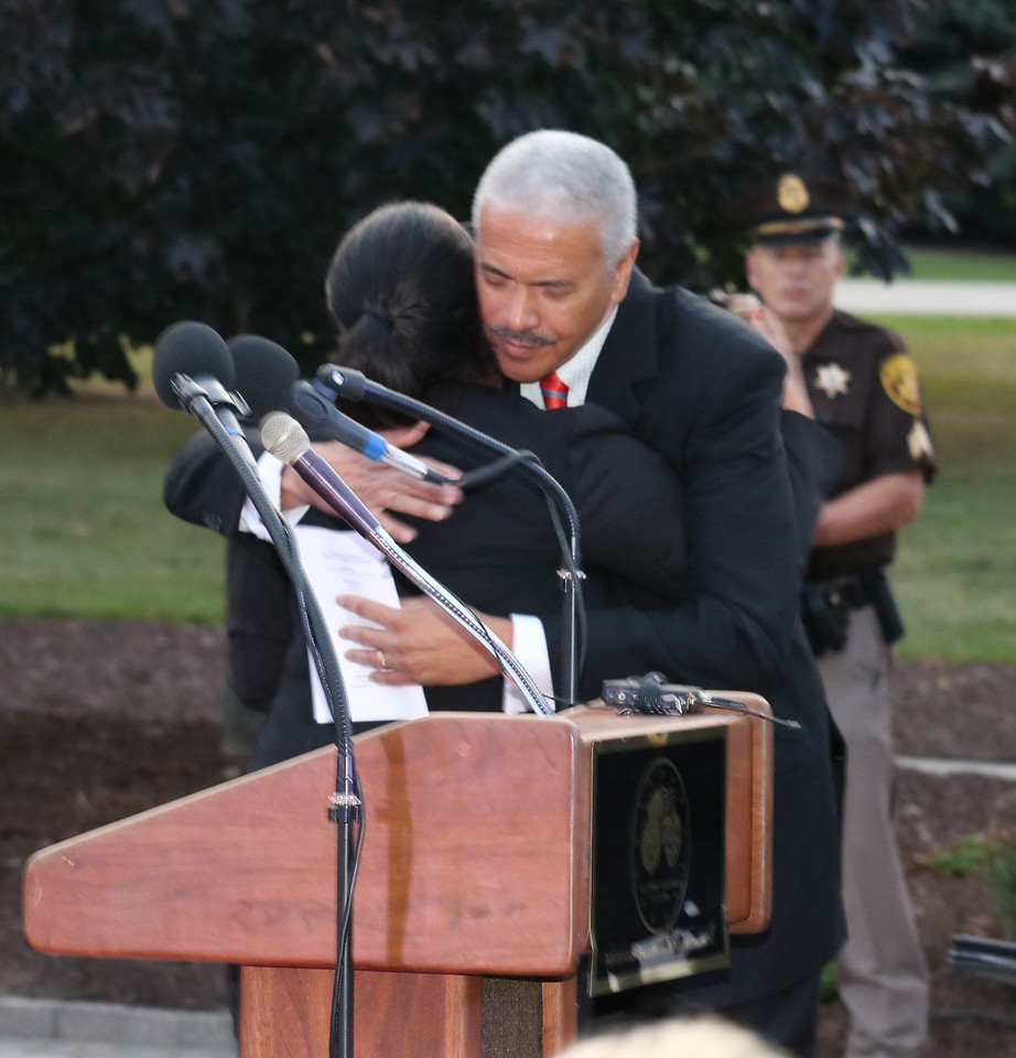 Emcee Huel Perkins embraces JoAnn Steil, whose husband, Kenneth Steil was shot to death while on duty with the Detroit Police Department.