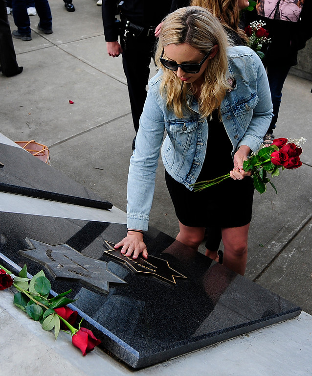 . FAIRFIELD,, CA - MAY 16, Jamie Trujillo touches the star on her father\'s memorial, Vallejo Police Officer Jim Capoot, during the 2018 Peace Officers\' Memorial Service on Wednesday in Fairfield. (Chris Riley/Times-Herald)