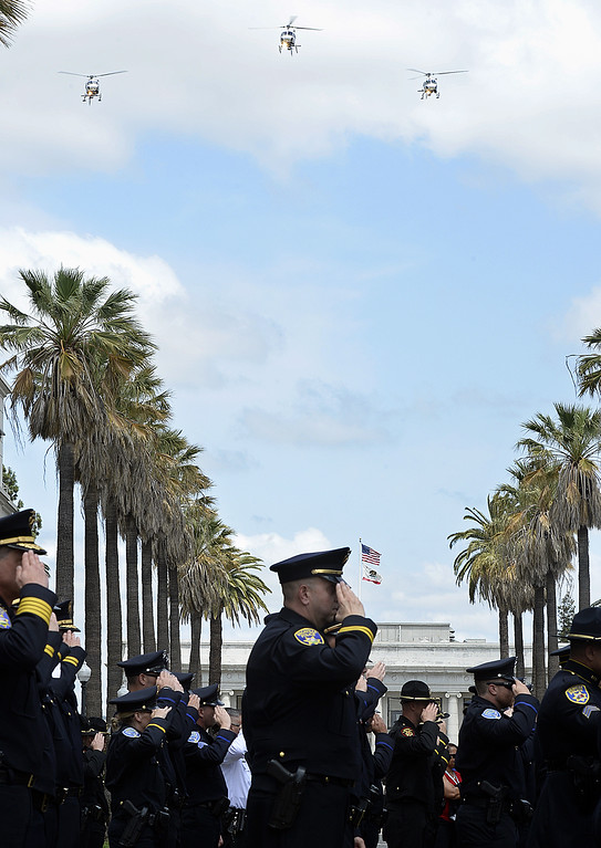 . Solano County law enforcement officers, salute at the conclusion of the 2018 Peace Officer\'s Memorial as California Highway Patrol helicopter perform a fly-over.  Joel Rosenbaum -- The Reporter