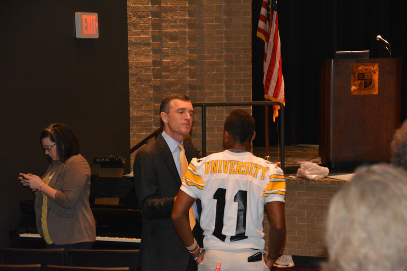 Burton speaks to a high school football player after the presentation.
