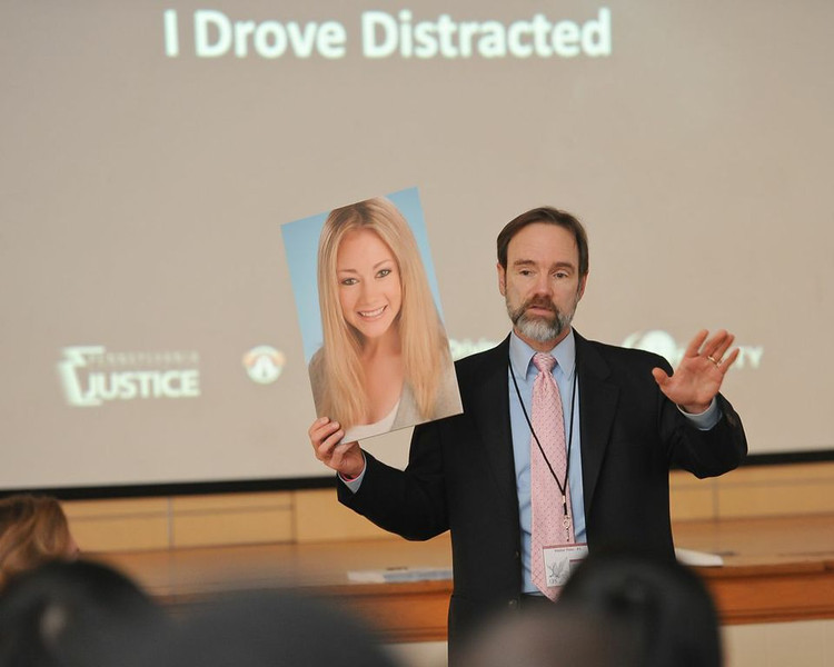 Joel Feldman, displaying a photograph of his daughter, Casey Feldman, as he admits to the students that he drove distracted.