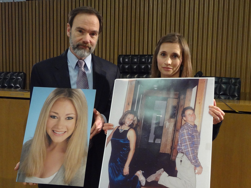 Joel Feldman and Emily Stein holding pictures of Casey Feldman and Howard Stein aft the press conference