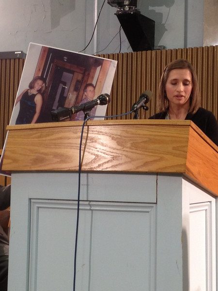 Emily Stein, victim's daughter, speaks at the press conference as she holds up a photo of her and her father