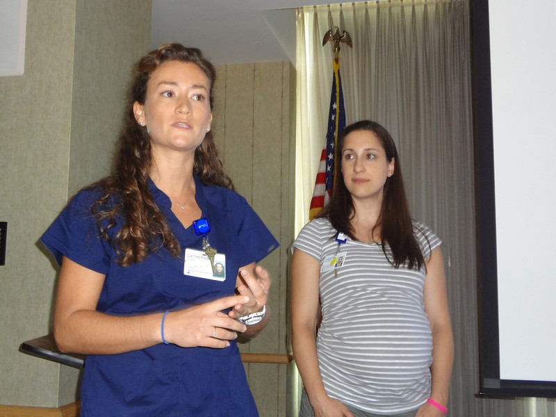 Occupational Therapist, Cate Dorr (L) speaks to the group of volunteers during the lunchtime ceremony about Ford and his work with patients as occupational therapist Christine Rineheimer, looks on.