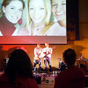 Amber Staska, Casey and Rachael Kemmey on the screen behind the musicians.