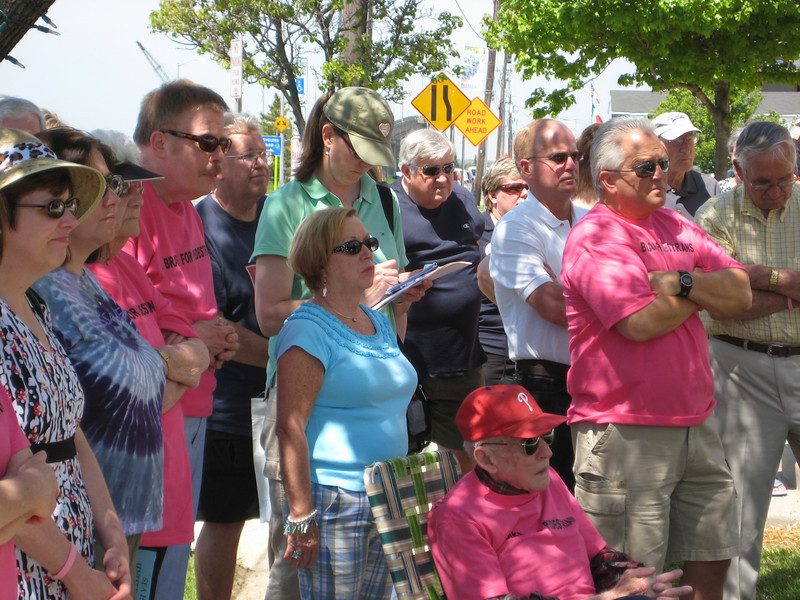 A local reporter takes notes as the crowd listens to the speakers.