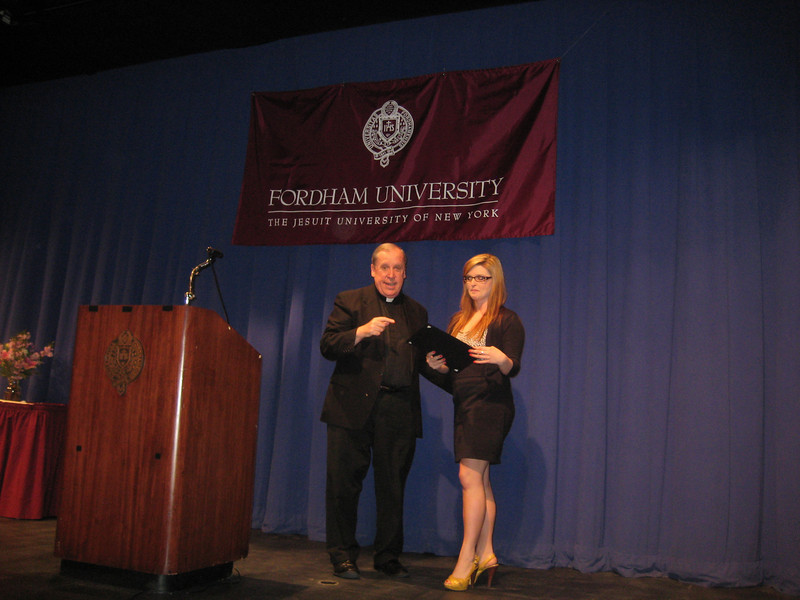 Stefanie Wheeler receiving the award from Rev. Michael Tueth, S.J.