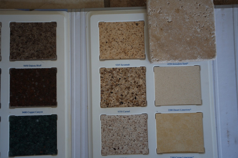 The Travertine backsplash we will use is the small piece of travertine tile in the upper right on top of the countertop samples.<br /> <br /> We are thinking of going with Carmel CaesarStone (manufactured quartz countertop -- similar to Home Depot's SileStone or Dupont's Zodiaq). <br /> <br /> It is on the right page of the sample book. Left column, second from the top -- looks dark cream peppered with brown and black bits.