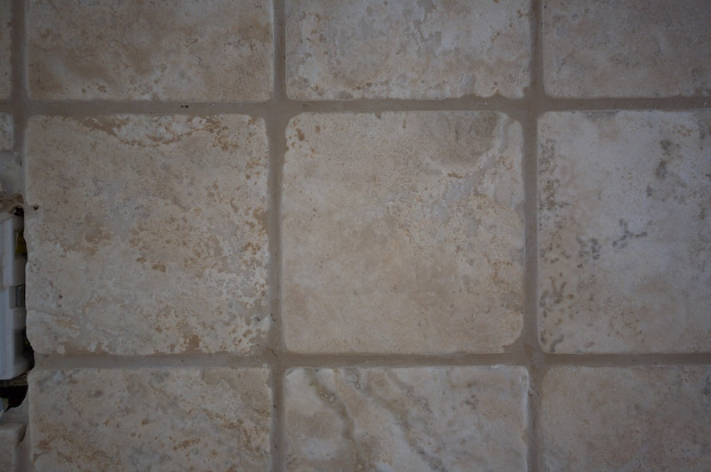 Travertine backsplash recently grouted. Grout has yet to dry to its final color.