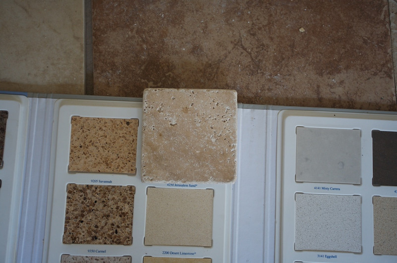 The Travertine floor sample is in the background. It is the darker one in the upper right behind the backsplash travertine sample.
