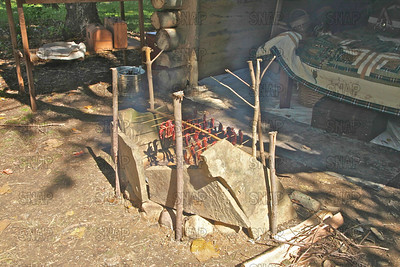 Smoking/cooking deer jerky over a low campfire.  The stones are used to contain, and reflect the heat, at the Pioneer Days festival in Fowler Park, near Terre Haute, IN.