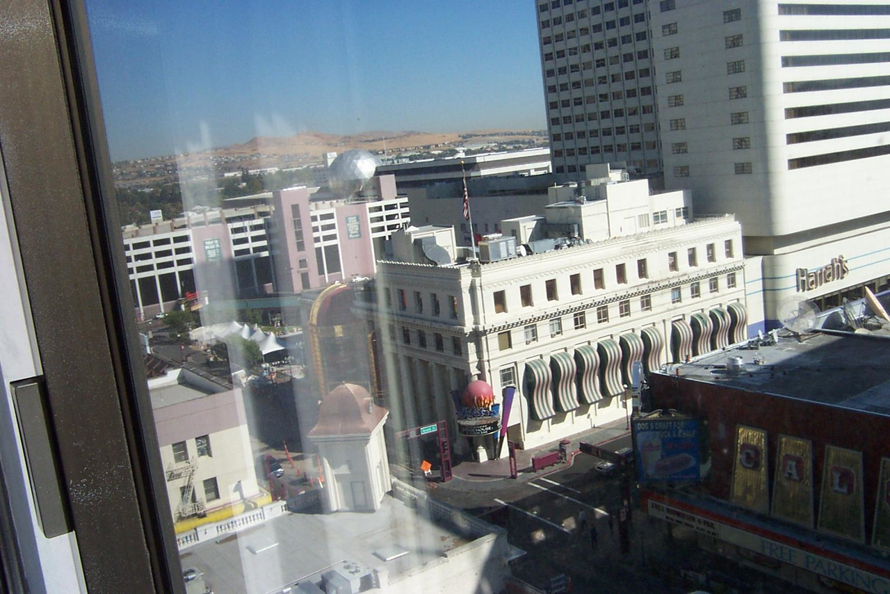 Another shot taken from Dave's Cal-Neva hotel room.  On the right, you can see one corner of the Cal-Neva casino, which is across the street from their hotel tower. The small white building across the street is part of Harrah's casino complex.  I think it was originally a bank building.<br /> [Reno]