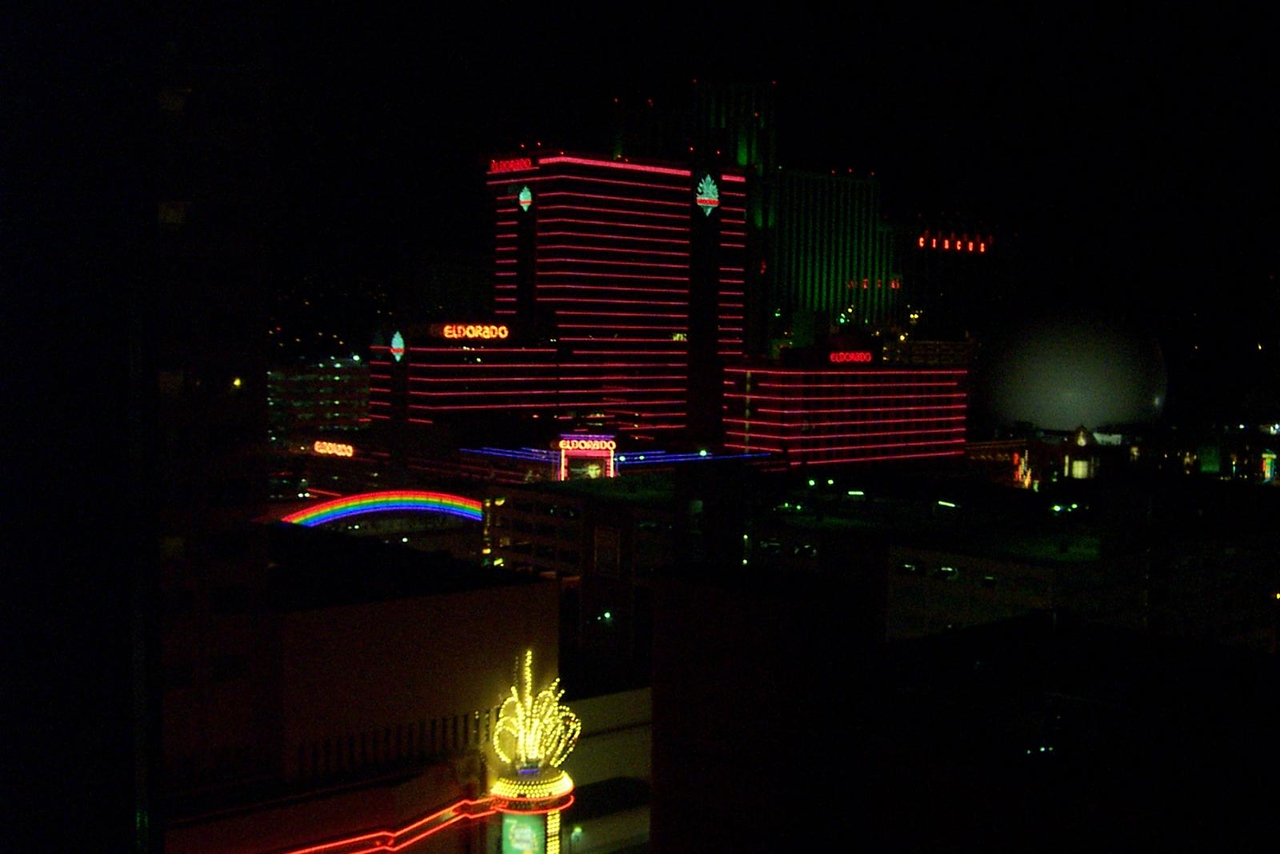 The nighttime view of the Eldorado from my East Tower room at Harrah's.  The green building behind it, and the dome at right are part of the Silver Legacy.<br /> [Reno]