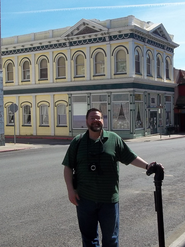 Jon and one of the hitching posts that still line West Miner Street.  Note the cool building in the background, too.<br /> Photo by Dave.<br /> [Yreka, CA]