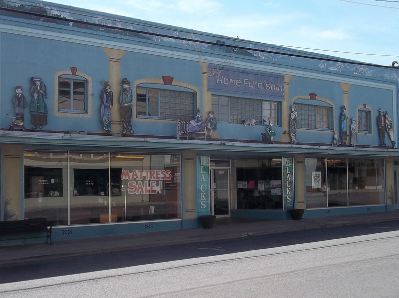 I liked the way this building was decorated.  On the second floor, there are actual objects (a tricycle, a bench, etc) together with the paintings of the people.<br /> [Yreka, CA]
