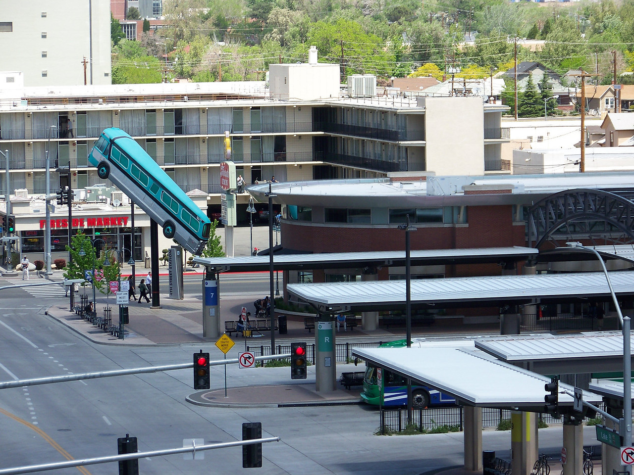 Since our last visit, they relocated the downtown transit center to the northeast of Harrah's.  I like the new sign (or is that art?) featuring an old-fashioned, turquoise-colored bus on a pole.<br /> [Reno - shot from Harrah's parking garage]