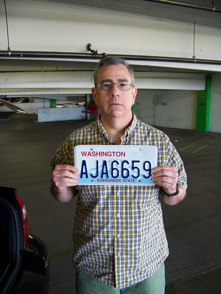 No, it's not a mug shot--we've never been arrested in Reno....yet!  :-)<br /> Dave's posing here with his car's front license plate before we left Harrah's garage.  He always removes the front plate before going through an automated carwash so the machinery won't mangle it.<br /> [Reno]
