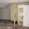 Bathroom in corner of basement with electric closet behind it.