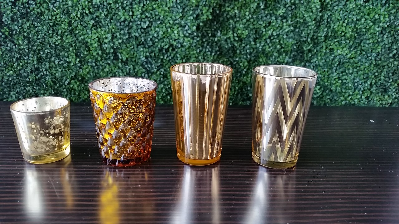 Our gold votive holder collection.  The striped & chevron patterned one is oversized and can be used as a small vase as well.