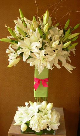 "Alter Table arrangement in 24""  square tall vase with partial lime green ribbon wrap and simple hot pink bow filled with white oriental lilies and curly willow"