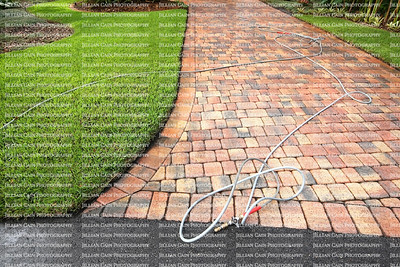 Paver driveway professionally pressure cleaned, with the hose and wand on the driveway.