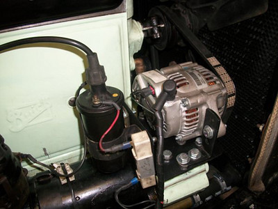 Modern alternator mounted on 25X.  A small Japanese 40amp unit that sits above and forward of the old generator.  A new, smaller pulley was fabricated to get around the crankshaft speed issue which is 1/2 engine speed.