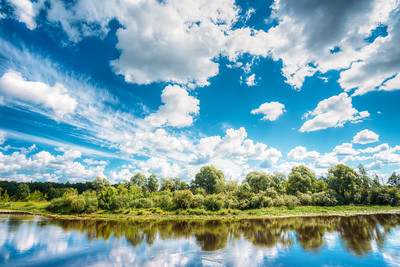 River Landscape With Reflections Of Clouds And Woods In Water. Summer. Sunny Day