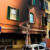 """7/6/09 17:32 Via del Borgo di San Pietro 23<br /> <br /> Forte incendio che coinvolge diversi motocicli, una auto e gli edifici circostanti. Un abitante della zona osserva i danni alle case. (Come era prima da Google Street View: <a href=""""http://tinyurl.com/muqh7s"""">http://tinyurl.com/muqh7s</a>)"""