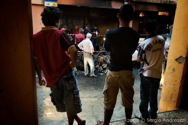 7/6/09 5:47 Via del Borgo di San Pietro 23<br /> <br /> Forte incendio che coinvolge diversi motocicli, una auto e gli edifici circostanti. Alcuni cittadini stranieri ed un uomo italiano osservano quello che rimane dei loro mezzi.