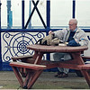 Eastbourne - man gets out a packed lunch and reading material on a grim and rainy day on the Pier.  Notice cracked pane of glass.