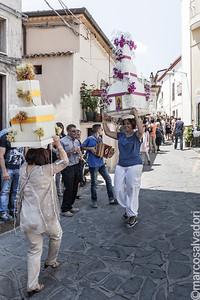 """Il trasporto delle """"cende"""": costruzioni votive di candele e nastrini portate sul capo. Le donne, durante la processione, ballano danze tipiche lucane."""