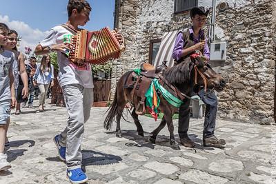 il paese in festa con i suonatori precede la processione e le offerte per il santo.