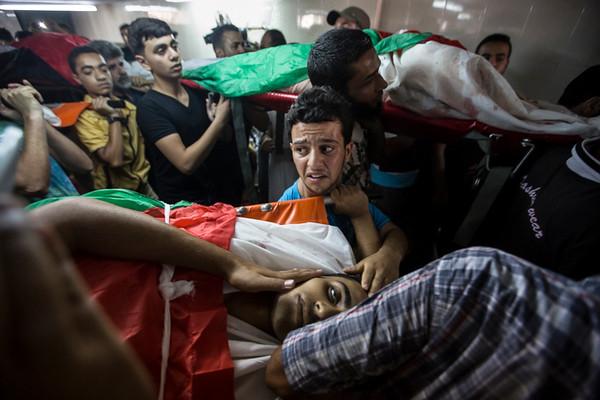PHOTO OLIVIER PONTBRIAND, LA PRESSE -  GAZA  - 19 Juillet 2014<br /> Sur cette photo: Une des neuf dépouilles quitte la mosquée dans un désordre total. Neuf cousins sont morts dans une même attaque plus tôt dans la journée.  Douzième jour des hostilités. Le nombre de morts augmente rapidement et la rage des Gazaouis se fait sentir.  -30-  <br />  <br /> PHOTO OLIVIER PONTBRIAND LA PRESSE. -  GAZA  -  July 19 2014<br /> In this picture: A man carries his brother from the mosque to the cemetery. Nine cousins were killed in the same attack earlier in the day. On the 12th day of Operation Protective Edge, the death toll is increasing fast and people in Gaza are voicing their anger. -30