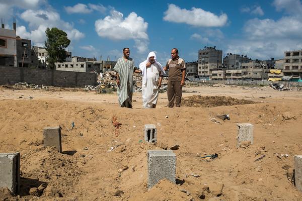 PHOTO OLIVIER PONTBRIAND LA PRESSE. -  GAZA  - 15 Juillet 2014<br /> Sur cette Photo:  Namen al-Batsh a été blessé et a perdu 18 membres de sa famille, dont sa femme et son frère, au début de l'opération israélienne dans la bande de Gaza. Ce muezzin de la mosquée du quartier d'Al-Sheja'iya  s'est recueilli sur leurs tombes improvisées, à quelques mètres de la maison familiale détruite. 30-  <br />  <br /> PHOTO OLIVIER PONTBRIAND LA PRESSE.  - Gaza strip - July 15 2014.<br /> In this Picture:  Namen al-Batsh was injured and lost 18 members of his family, including  his wife and his brother, in the beginning of the Israeli operation. This muezzin from the nearby mosque in the Al-Sheja'iya neighborhood went to visit their makeshift tombs, meters from the destroyed family house.