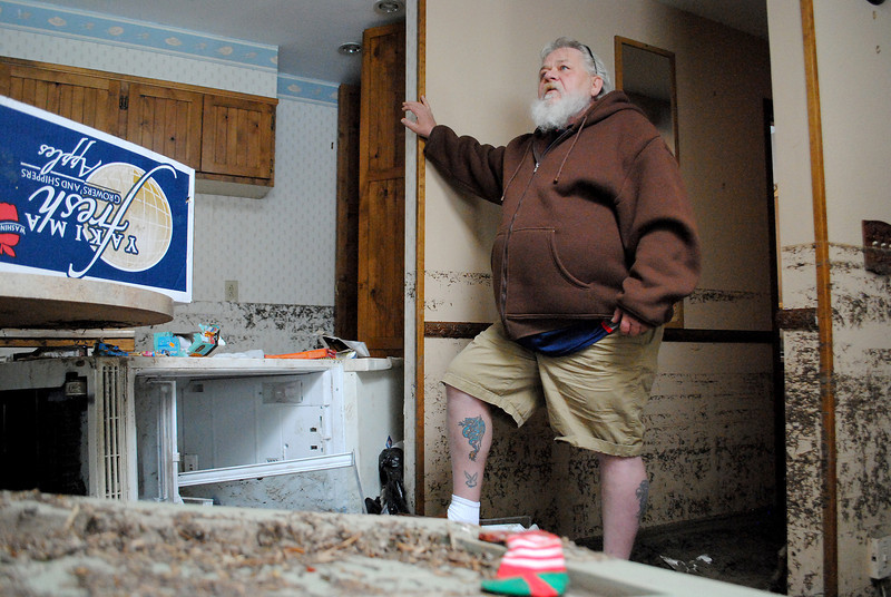 Patrick Losee looks over the damage caused by the flood to his home near Glen Haven Sunday Nov. 24, 2013. The water level reached 8 feet inside his home, and him and his girlfriend where forced to escape out the skylight.  (Photo by Lilia Munoz/ Loveland Reporter-Herald)