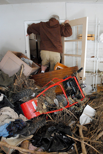 Patrick Losee climbs over debris left over by the flood to be able to get into his home near Glen Haven Sunday Nov. 24, 2013.  (Photo by Lilia Munoz/ Loveland Reporter-Herald)