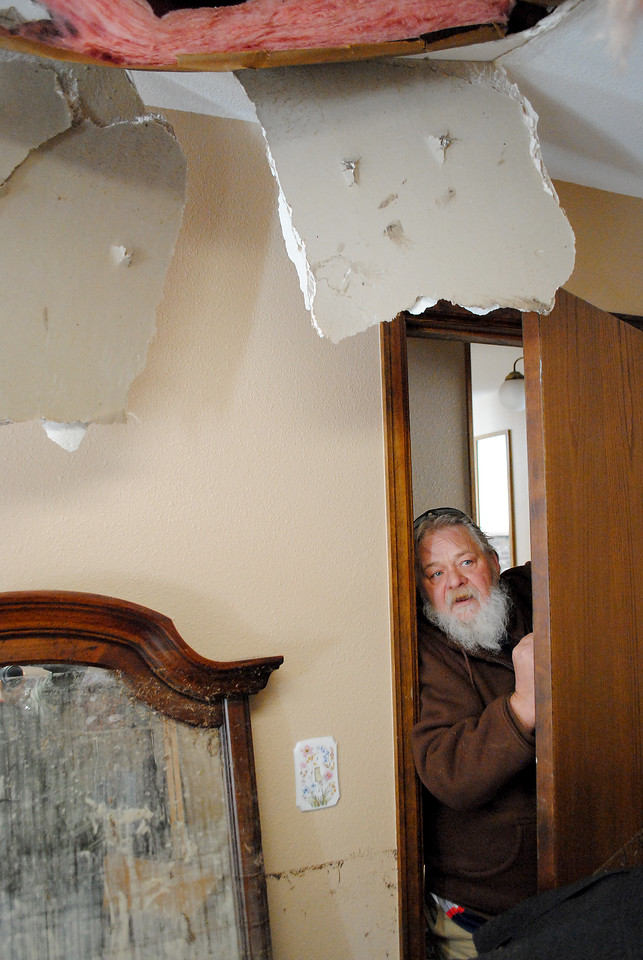 Patrick Losee looks at the damage inside what used to be his bedroom at his home near Glen Haven Sunday Nov. 24, 2013.  (Photo by Lilia Munoz/ Loveland Reporter-Herald)