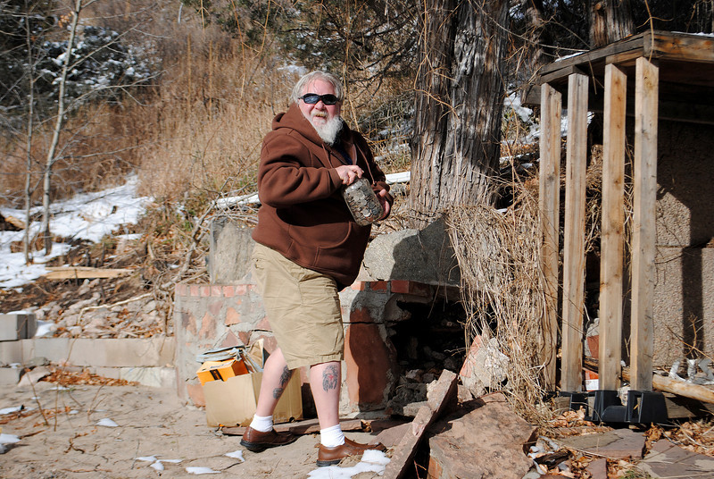Patrick Losee pulls out a jar of coins that survived the flood, he had hidden it for his grandchildren outisde his home by near Glen Haven Sunday Nov. 24, 2013.  (Photo by Lilia Munoz/ Loveland Reporter-Herald)