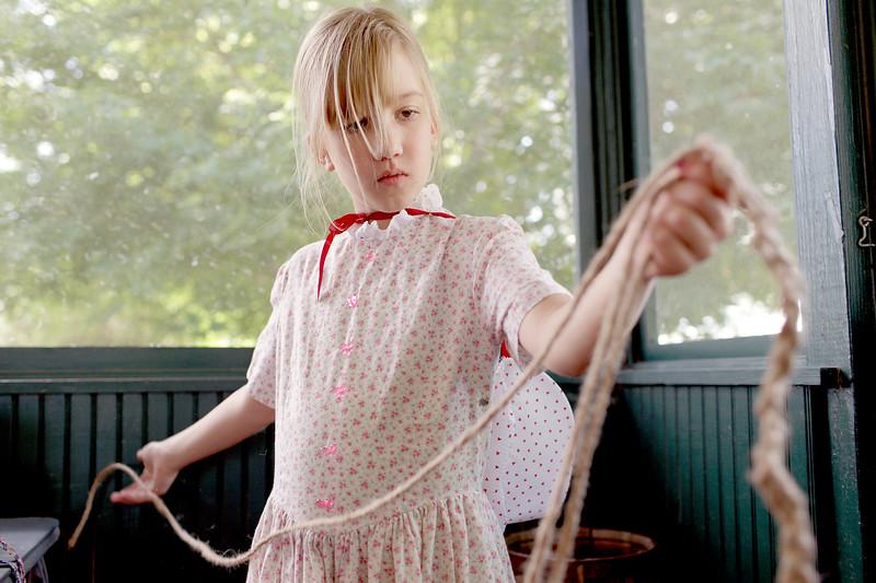 Nine-year-old, Linda Pugh Wacha braids twine at Timberlane Farm Museum's History Time Traveler Camp on July 17, 2015 in Loveland, CO. (Photo by Trevor L Davis/Loveland Reporter-Herald)