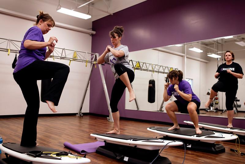 Ann Kessler, Meredith Welty, Morgan Riedl and Rebecca Godin exercise on Surfset boards at Anytime Fitness in Loveland on Thursday, Oct. 15, 2015. (Photo by Trevor L Davis/Loveland Reporter-Herald)