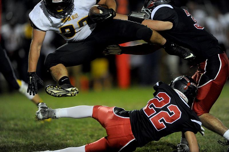 Patton Graff (32), top, running back for Thompson Valley, jumps over Kaden Morin (22), defensive back for Loveland high, in the second half on Friday, Oct. 16, 2015 in Loveland. (Photo by Trevor L Davis/Loveland Reporter-Herald)