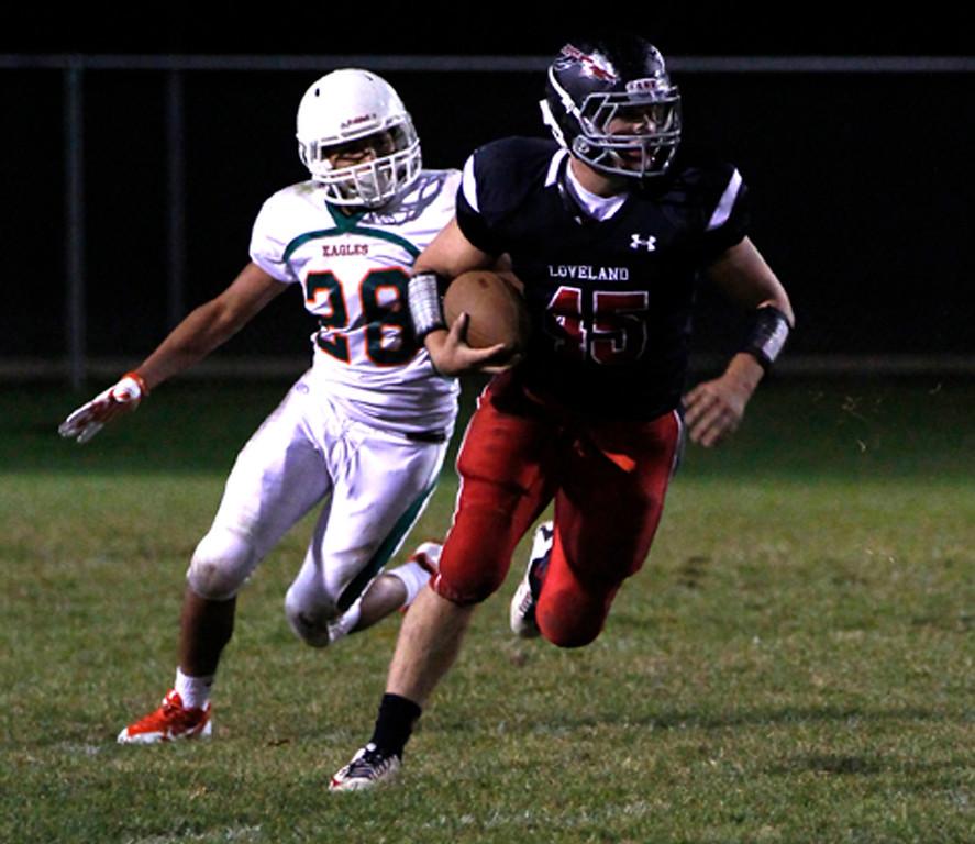 Ryan Svendsen of the Loveland Indians runs the ball avoiding a tackle by the Eagles, Joseph Gonzalez on Friday 30, 2015. (Photo by Matthew Gaston/Loveland Reporter-Herald)