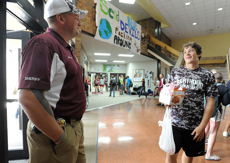 Larimer County Sheriff's office deputy Ray Meyer, left, the school resource officer at Berthoud High School, chats with freshman Ty Beaman, 14, right, during lunch period at the school Friday, Sept. 18, 2015. (Photo by Jenny Sparks/Loveland Reporter-Herald)