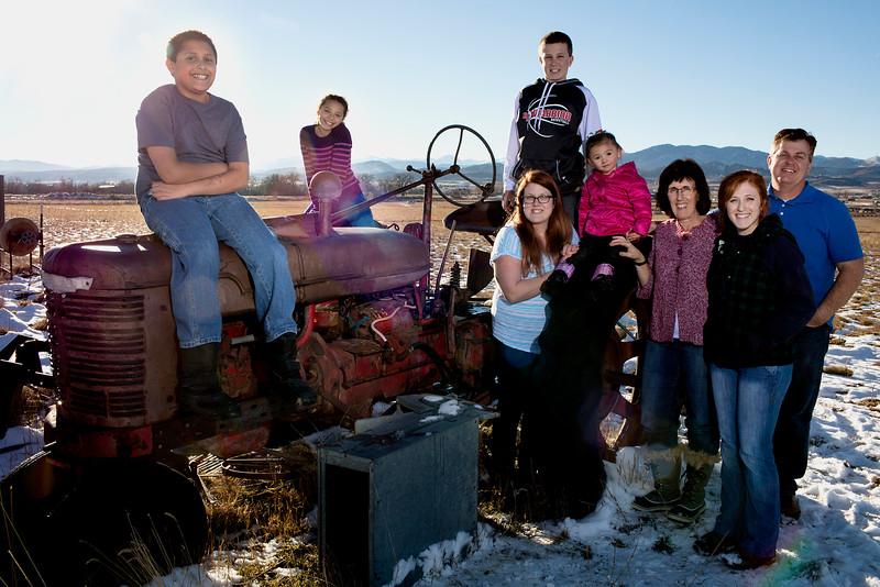 From left, Eli, Mya, Rebeccah, Landon, Ava, Ronda, Hannah and Joe Carlson pose for a portrait on a tractor in their back yard on Sunday, Dec. 13, 2015 in Loveland. (Photo by Trevor L. Davis/Loveland Reporter-Herald)