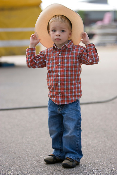 Caleb Brannan, 3, stares off at the rides while waiting in line to ride the Ferris wheel with his parents, sister and grandmother.