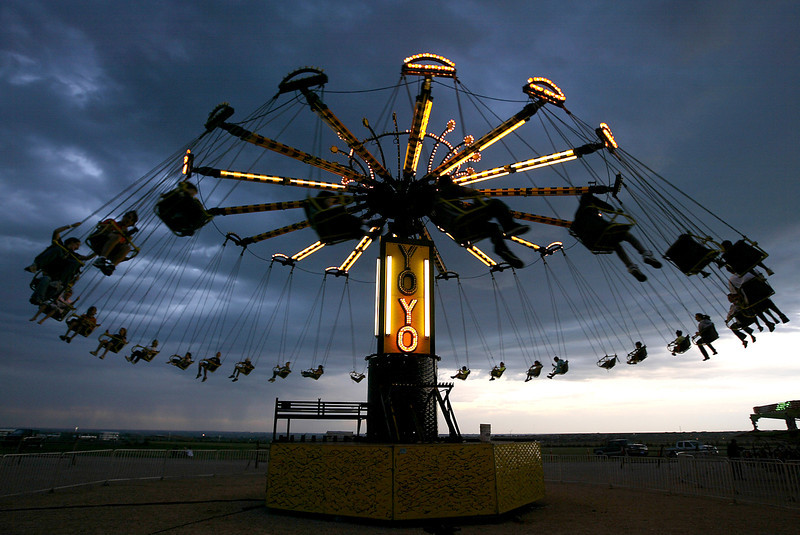 Fairgoers ride the YoYo at dusk.