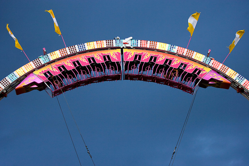 People ride the Ring of Fire as rain clouds loom in the background.