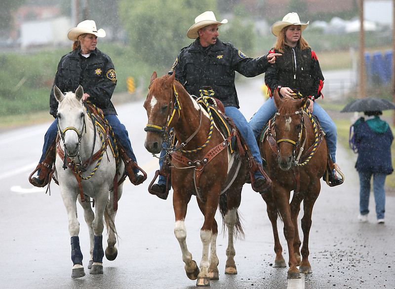 From right to left, Larimer County Sheriffs Posse, Barb Bowman, James Remington, and Larimer County Sheriffs Posse Queen, Emily Arbery, ride their horses through the rain before the parade starts.