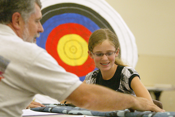 Shelby Lynne, 10, from Loveland, shows her archery bag to Ken Yoder, a representative from Fort Collins Archery Association, during her 4-H shooting sports interview Tuesday at the Lairmer County Fair.