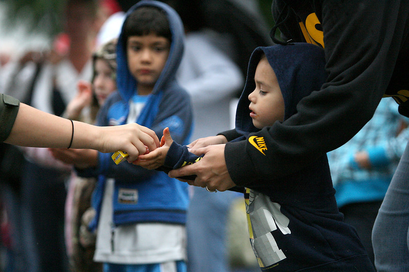 Katrina Hernandez helps her son Athan, 2, take candy from a parade participant.